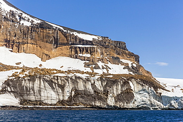 Rust-colored volcanic tuff cliffs above a dark material filled glacier at Brown Bluff, eastern side of the Tabarin Peninsula, Weddell Sea, Antarctica, Polar Regions