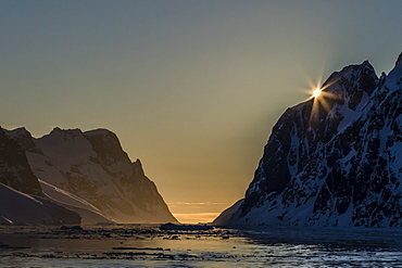Sunset over Booth Island in the waters of the Lemaire Channel, Antarctica, Polar Regions