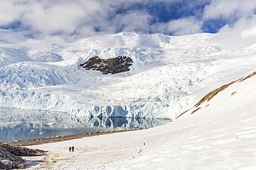 Two hikers surrounded by ice-capped mountains and glaciers in Neko Harbor, Antarctica, Polar Regions
