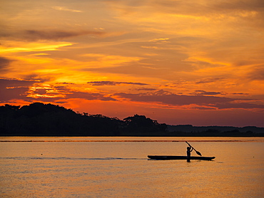 Young man paddling his fishing boat at sunset over calm waters on Clavero Lake, Amazon Basin, Peru, South America