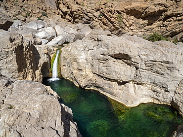 Waterfall dropping in to naturally formed swimming pools in Wadi Bani Khalid, Sultanate of Oman, Middle East