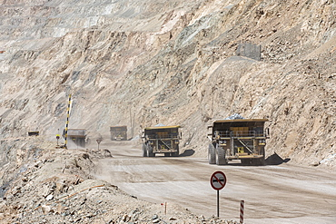 Huge dump trucks working the Chuquicamata open pit copper mine, the largest by volume in the world, Chile, South America