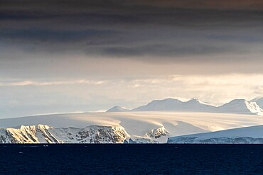 Sunrise on snow-covered mountains and tidewater glaciers in Mikkelsen Harbor, Trinity Island, Antarctica, Polar Regions