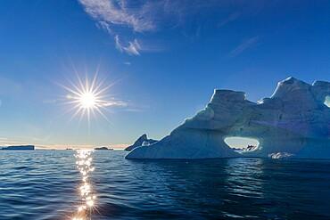 Sunburst on iceberg in De Dodes Fjord (Fjord of the Dead), Baffin Bay, Greenland, Polar Regions