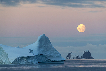 Nearly full moon setting over small islands and icebergs off the Trinity Peninsula, Antarctica.