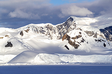 Shorefast ice and snow covered mountains in early season in Wilhamena Bay, Antarctica.