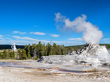 Castle Geyser steaming, with Old Faithful erupting behind, in Yellowstone National Park, Wyoming, USA.