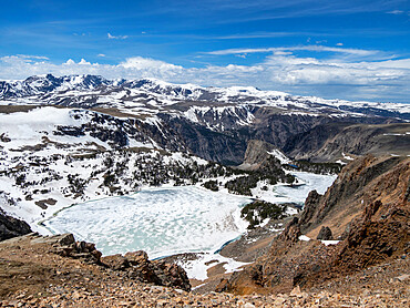 Snow-capped mountains and a frozen lake near Beartooth Pass, Wyoming, USA.