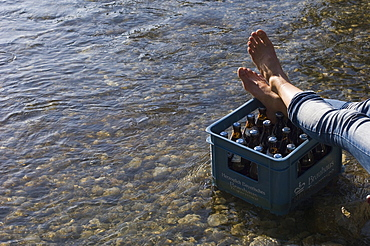 Person resting his feet on a crate of beer, River Isar, Munich, Bavaria, Germany