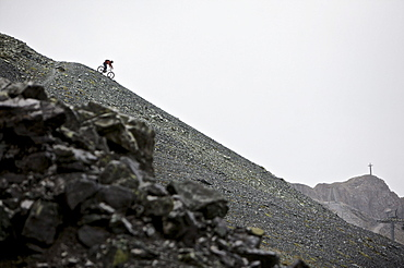 Mountainbiker riding down a scree in the mountains, Ischgl, Tyrol, Austria