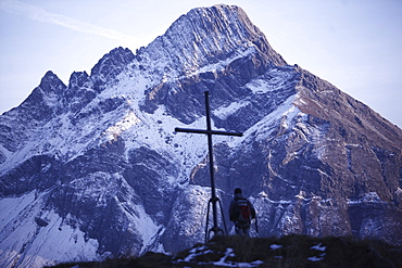 Man standing at a cross on the summit of a mountain with view of the Alps, Oberstdorf, Bavaria, Germany