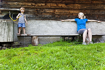 Woman and child on a bench infront of a farmhouse, Kloaschau Valley, Bayrischzell, Bavaria, Germany