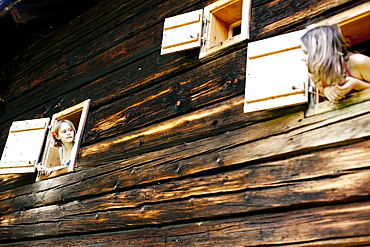 Two girls looking out of farmhouse, Styria, Austria