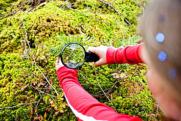 Girl looking at plant through magnifying glass, Styria, Austria