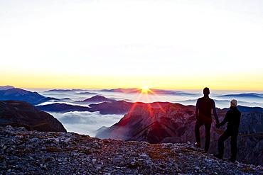 Two hikers at summit of Hochschwab mountain at sunrise, Hochschwab, Styria, Austria - 1113-104353