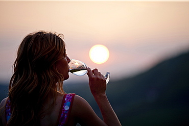 Young woman drinking a glass of white wine in sunset, Riegersburg, Styria, Austria