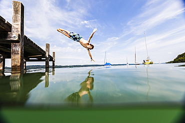 Boy jumping into lake Starnberg, Bavaria, Germany