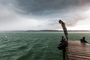 Young man on a jetty leaning into the wind, Lake Starnberg, Bavaria, Germany