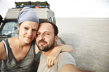 Couple posing in front of an off-road vehicle, Kubu Island, Makgadikgadi Pan, Botswana