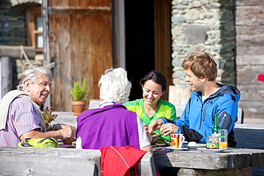 Four hikers having a snack in front of an alpine hut, Styria, Austria