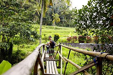 Woman passing a bamboo bridge, Karangasem, Bali, Indonesia