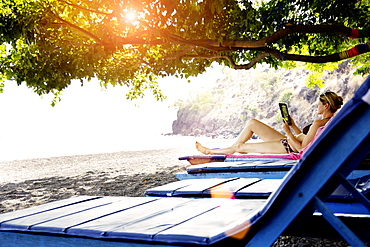 Woman lying on a beach chair while reading, Amed, Bali, Indonesia