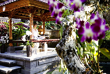 Woman meditating in a pavilion, Ubud, Bali, Indonesia