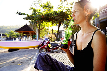 Woman drinking a bottle of beer at beach, Padangbai, Indonesia