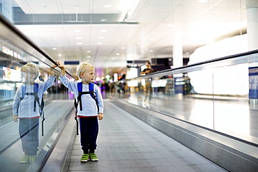 Boy standing on a moving walkway at airport