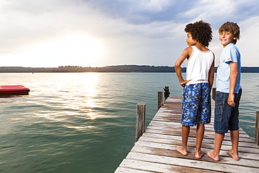 Two boys on a jetty at lake Starnberg, Upper Bavaria, Germany