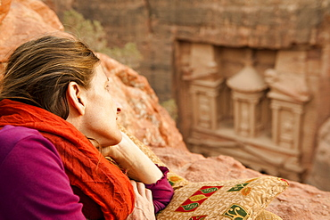 Woman lying on rock, Al Khazneh in background, Petra, Jordan, Middle East