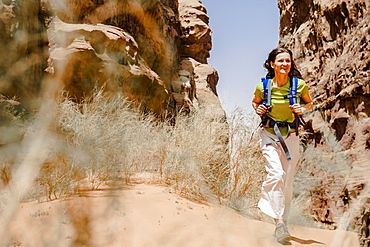 Woman hiking through a gorge, Wadi Rum, Jordan, Middle East