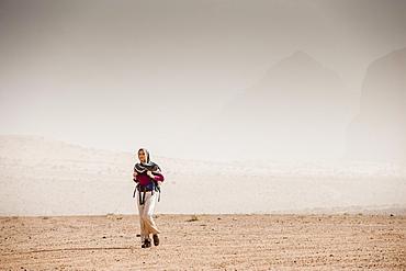 Woman hiking through desert scenery, Wadi Rum, Jordan, Middle East