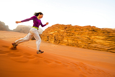 Woman running a sand dune down, Wadi Rum, Jordan, Middle East