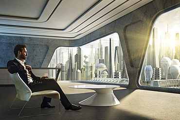 Man sitting inside a modern appartment and looking at a futuristic city skyline, Germany