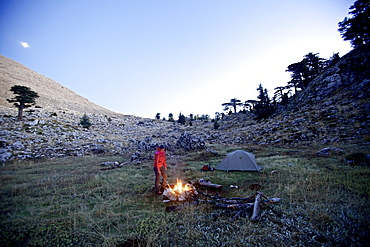 Woman standing at a campfire, long-distance footpath Lycian Way, Antalya, Turkey