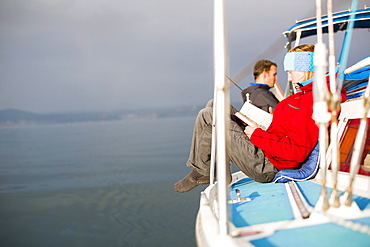Woman reading on the deck of a sailing boat, Gulf of Trieste, Gorizia, Friuli Venezia Giulia, Italy