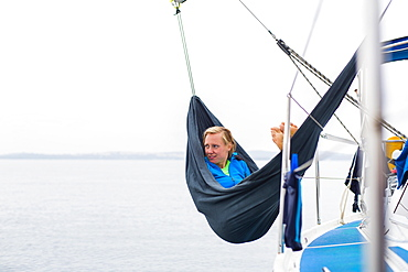 Woman relaxing in a hammock on board of a sailing boat, Pula, Istria, Croatia