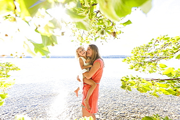 Mother carrying daughter in her arms, lake Starnberg, Berg, Upper Bavaria, Germany