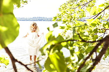 Girl wearing a summerdress standing in lake Starnberg, Berg, Upper Bavaria, Germany