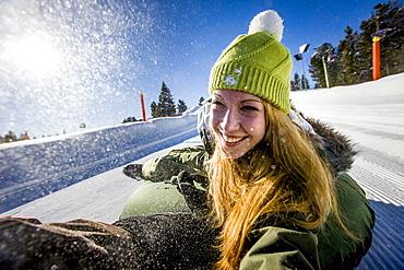 Young woman snow tubing, Kreischberg, Murau, Styria, Austria