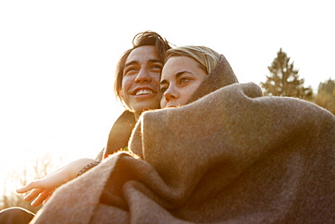 Young couple wrapped in a blanket, Grosser Alpsee, Immenstadt, Bavaria, Germany