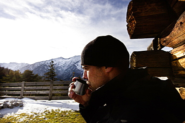 Hiker taking a rest and drinking out of a cup, Koegl alp (1432 m), descent from Unnutz Mountain (2078 m), Rofan Mountains, Tyrol, Austria