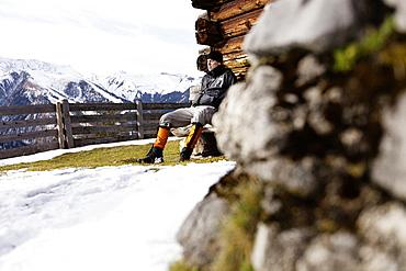 Hiker taking a rest, Wooden alpine hut, descent from Unnutz Mountain (2078 m), Rofan Mountains, Tyrol, Austria