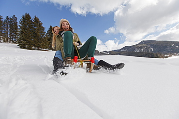 Two young women downill sledding, Spitzingsee, Upper Bavaria, Germany