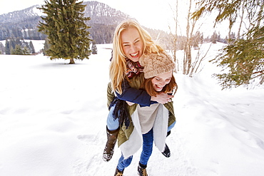 Young woman giving friend a piggyback ride, Spitzingsee, Upper Bavaria, Germany