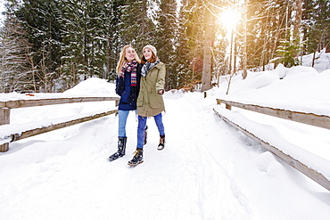 Two young women walking in snow, Spitzingsee, Upper Bavaria, Germany