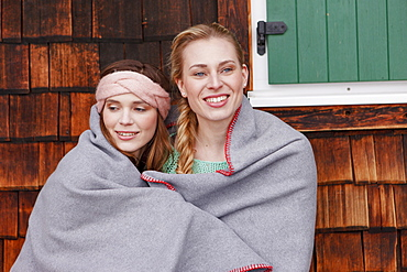 Two young women wrapped in a blanket, Spitzingsee, Upper Bavaria, Germany