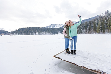 Two young women on jetty photographing themselves, Spitzingsee, Upper Bavaria, Germany