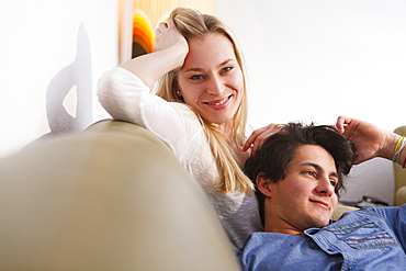 Young couple relaxing on the sofa, Embrassing